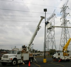 site lighting maintenance - Worker in a truck working on a parking lot light pole