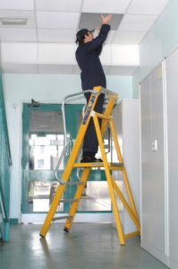 An Industrial Electrician You Can Trust - Worker on a ladder checking a light bulb on the ceiling
