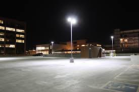 site lighting maintenance - bright parking lot light in empty parking lot at night