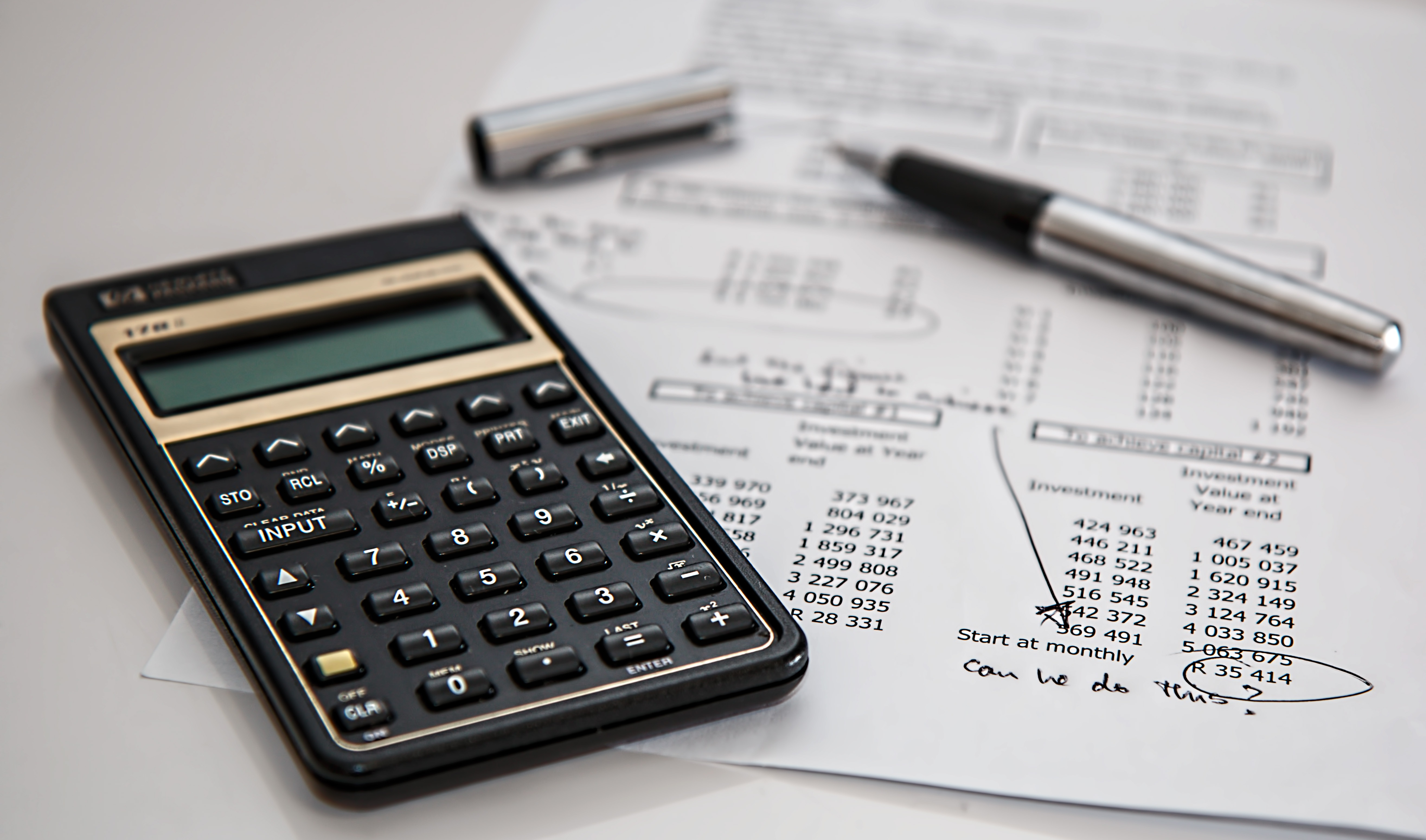 cost-effective maintenance - image of accounting items on a desk including calculator, pen, and paper financial report