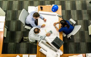 planned maintenance services - image shows overhead view of three people sitting around blueprints at a desk